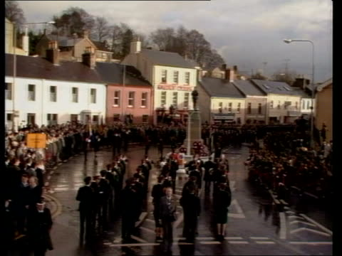Enniskillen remembrance service NORTHERN IRELAND Co Fermanagh Enniskillen MS War memorial with statue on top with crowd lining road in b/g TGV Crowds...