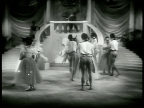 vidéos et rushes de ensemble walking up staircase down other side masked stranger stops the woman bows takes her hand she moves away down staircase ensemble ballet... - 1952