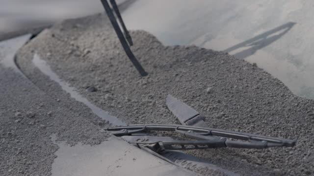 ensenada, chile-april 25, 2015: cu windscreen wipers, dirty windscreen of car stuck in volcanic ash - windschutzscheibe stock-videos und b-roll-filmmaterial