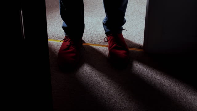 Entering a dark room, man's feet high angle view. DS