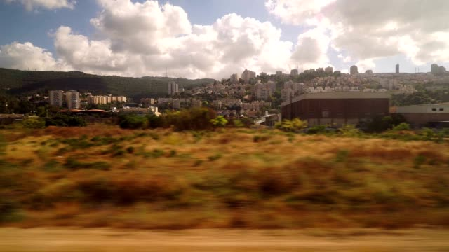 entering the city of haifa by train on a cloudy spring day - haifa video stock e b–roll