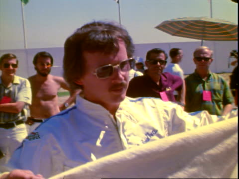 entertainer and motor sports enthusiast dick smothers wearing white racing suit, mustache and sunglasses while laughing, smiling, joking, talking... - veicolo di terra per uso personale video stock e b–roll