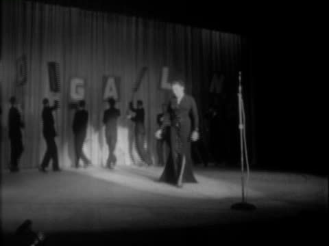 entertainer judy garland wearing long black evening gown + taking stage for performance at nightclub / male dancers in matching black tuxedos hold +... - letter b stock videos & royalty-free footage