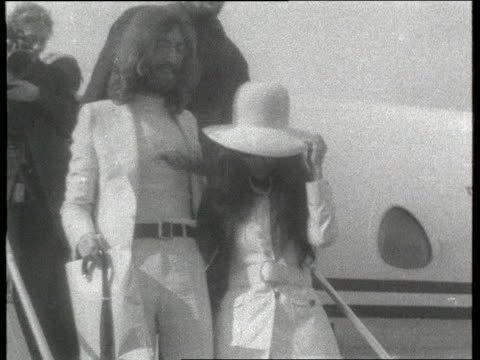 John Lennon Files Civil Liberties Union Takes Case to Court ITN W 1960s Footage John Lennon and wife Yoko Ono towards down steps from aeroplane MSs...