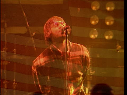 entertainment/accidents: oasis car crash; lib usa: michigan: detroit: ext liam gallagher performing on stage with us flag superimposed fade to... - オアシス点の映像素材/bロール
