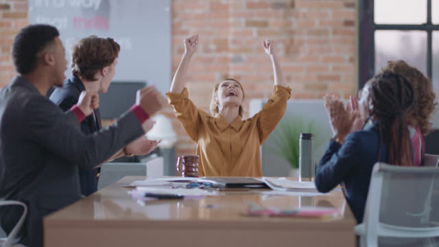 vidéos et rushes de enthusiastic business partners hug and high-five after a team meeting - collègue
