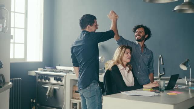 vídeos de stock e filmes b-roll de enthusiastic employees high-fiving at the office (slow motion) - criar laços