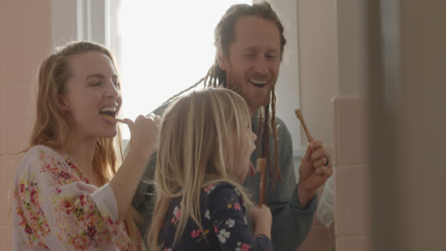 enthusiastic family brushes their teeth together in the bathroom - domestic bathroom stock videos & royalty-free footage
