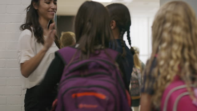 enthusiastic teacher greeting students entering doorway to classroom / provo, utah, united states - lehrkraft stock-videos und b-roll-filmmaterial