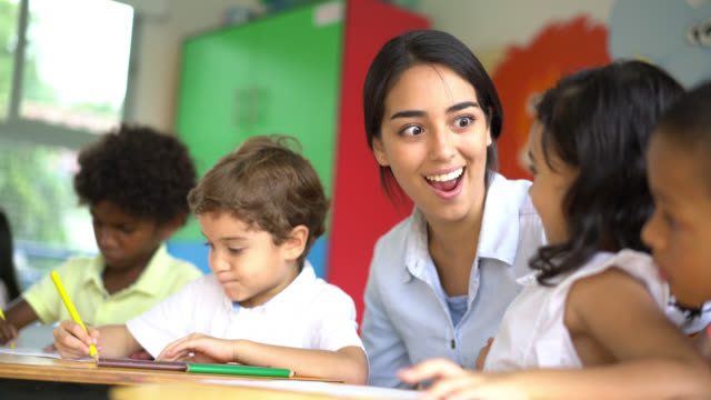 enthusiastic teacher helping her students at class - aula video stock e b–roll