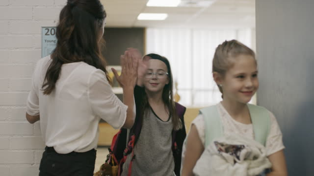 enthusiastic teacher high-fiving students exiting doorway from classroom / provo, utah, united states - kind im grundschulalter stock-videos und b-roll-filmmaterial