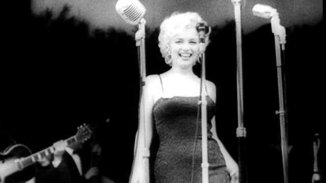 stockvideo's en b-roll-footage met enthusiastic troops waiting for marilyn monroe to perform / marilyn coming out on stage to perform for troops waving to the crowd approaching... - marilyn monroe