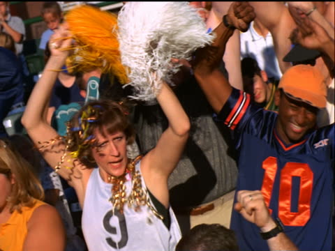vidéos et rushes de canted enthusiastic woman with pom-poms cheering in crowded stadium - acclamation de joie