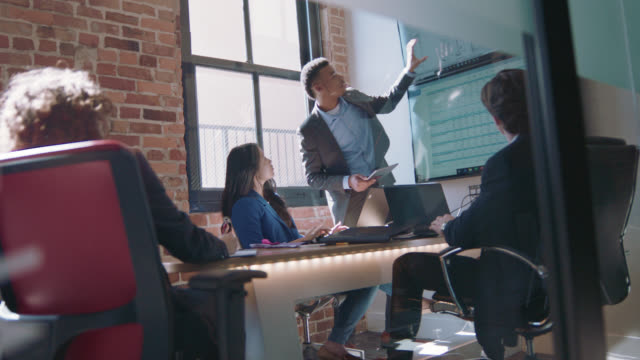 enthusiastic young african-american businessman leads meeting, points at spreadsheet data on large monitor - symbol stock-videos und b-roll-filmmaterial