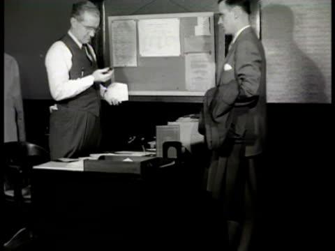 entrance 'acme battery co.' int vs inspector talking to acme battery employee at desk examining bomb remains '... this is one of our c-7 dry cell... - batteri bildbanksvideor och videomaterial från bakom kulisserna