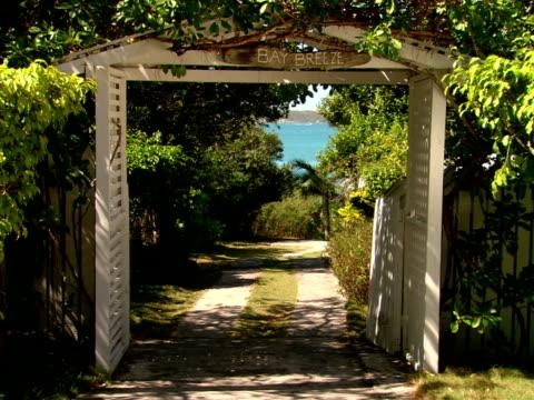 vídeos y material grabado en eventos de stock de ms,  entrance gate amongst lush foliage,  harbour island,  bahamas - escritura occidental