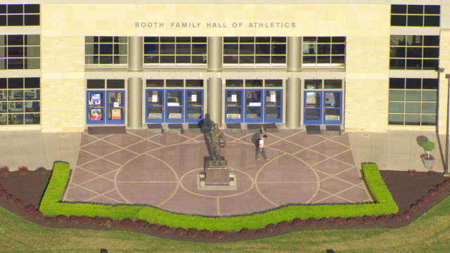 ms aerial entrance of booth family hall of athletics with phog allen statue / lawrence, kansas, united states - male likeness stock videos & royalty-free footage