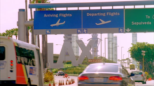 WS Entrance of LAX with arriving and departing signs, traffic on foreground / Los Angeles, California, USA