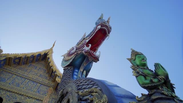 entrance of wat rong suea ten (blue temple) in chiang rai, thailand, southeast asia, asia - 竜点の映像素材/bロール