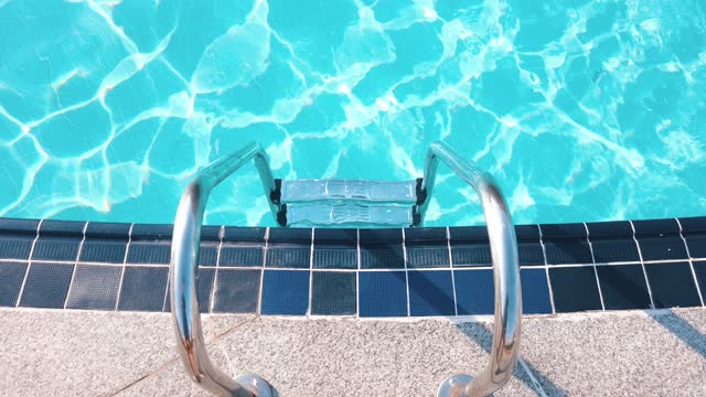 entrance pool ladder and shiny swimming pool water on the sunny day - poolside stock videos & royalty-free footage