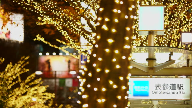 entrance sign of tokyo metro omote-sando station, which is surrounded by rows of illuminated tree in the night at kitaaoyama, minato tokyo japan on december 06 2017. tree lined omotesando street is decorated and illuminated for winter holydays seasons. - イルミネーション点の映像素材/bロール
