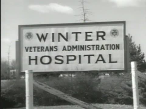 entrance sign to veteran's administration winter hospital int va hospital ward w/ psychiatric doctors nurses talking to us veterans patients - psychiatric hospital stock videos and b-roll footage