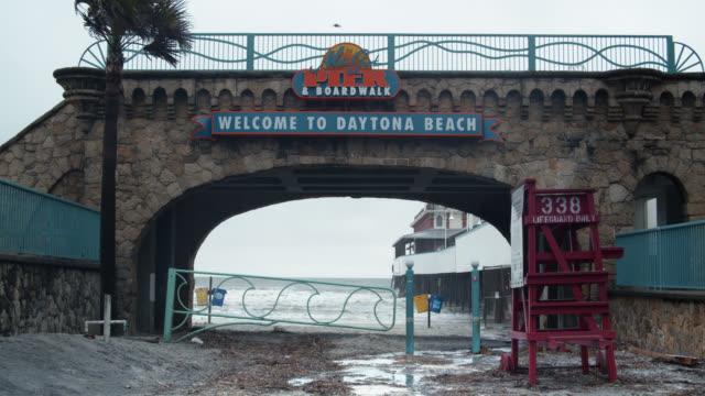 entrance to daytona beach, florida on stormy day - cabina del guardaspiaggia video stock e b–roll