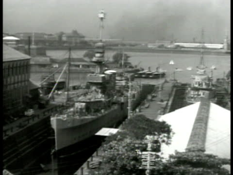 entrance to docks crowded w/ people destroyer in drydock indian males working repairing ship hammering hull removing paint welding turret wwii... - militärschiff stock-videos und b-roll-filmmaterial