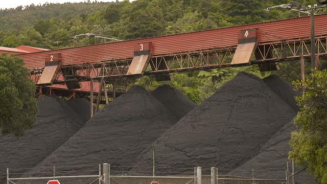 vidéos et rushes de entrance to stockton coal mine with signage perimeter fencing and piles of coal beneath conveyor - indication de direction
