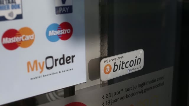 entrance to the spar arnhem centraal supermarket in arnhem netherlands on wednesday dec 17 various shots a bitcoin sticker is fixed to a window of... - bitcoin stock videos & royalty-free footage