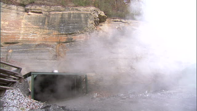 Entrance to underground coal mine gray/white smoke rising out of Appalachian Mountains rockface tunnel No People no miners Natural resource energy...