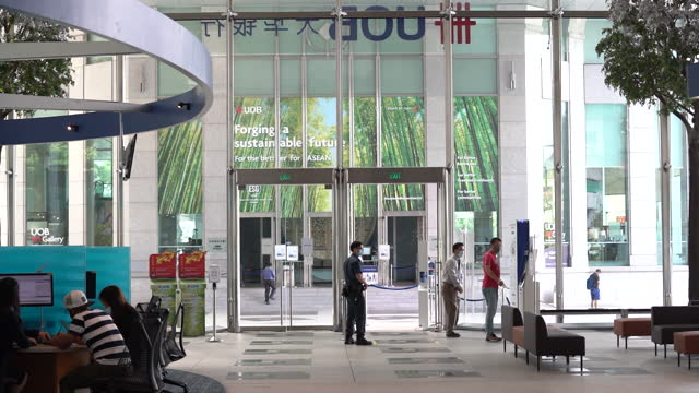 entrance to united overseas bank ltd. main branch at uob plaza seen from inside. uob's chief executive officer wee ee cheong cast an optimistic tone... - singapore stock videos & royalty-free footage