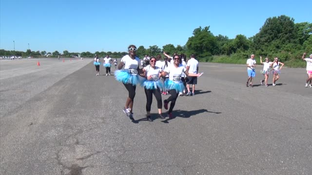 vidéos et rushes de entrants jog their way to color stations of red, purple, blue and yellow, very festive - concurrent