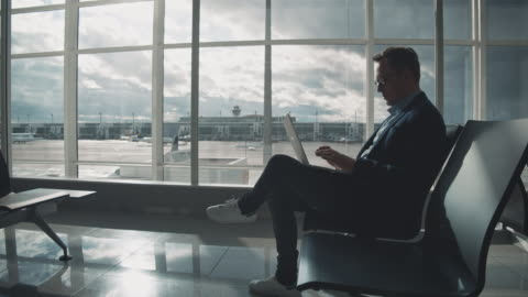 entrepreneur using laptop while waiting at airport - only men stock videos & royalty-free footage