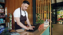 Entrepreneur working with laptop in flower shop typing and writing in notebook