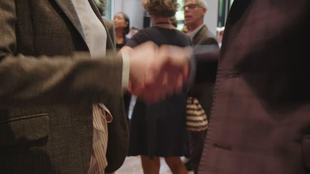 unternehmer schütteln bei hotelkonferenz die hand - konferenzzentrum stock-videos und b-roll-filmmaterial