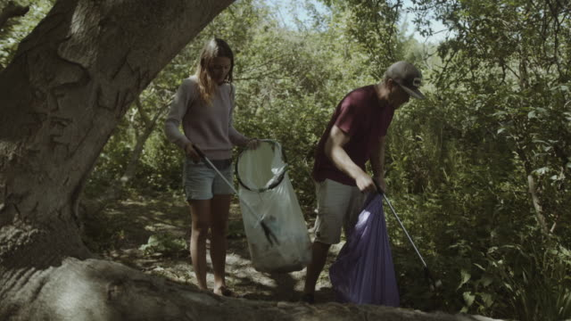 environmental activist collecting garbage with a trash grabber stick in forrest with dog walking on their walk - protection stock videos & royalty-free footage