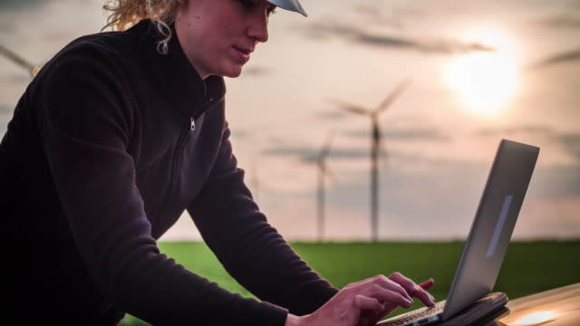 environmental engineer with laptop in front of wind turbines - women in stem - energia rinnovabile video stock e b–roll