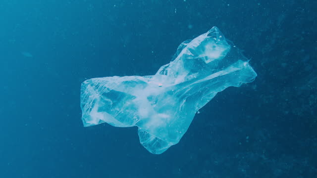 environmental issue: underwater footage of plastic in the ocean - bottiglia video stock e b–roll