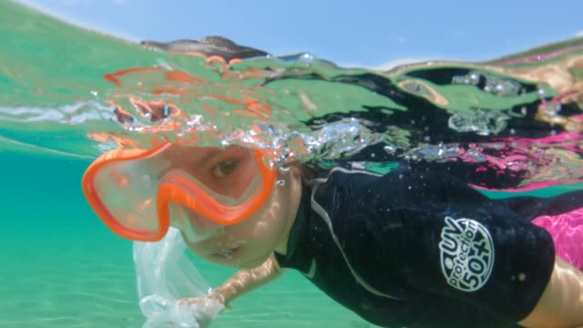 umweltprobleme: kind reinigt den ozean, entfernt plastiktüten. - auf dem wasser treiben stock-videos und b-roll-filmmaterial