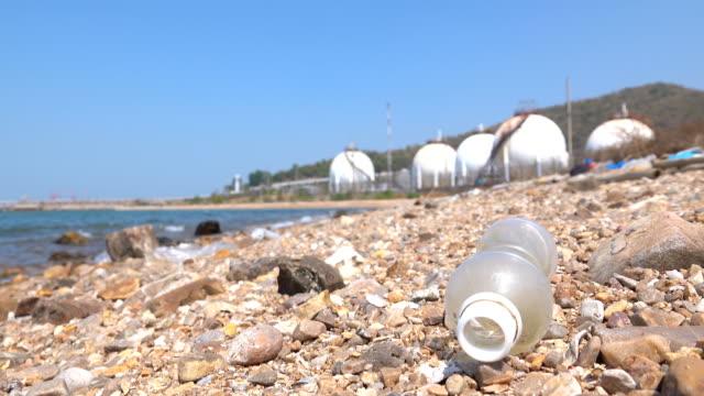 vídeos de stock e filmes b-roll de environmental pollution, plastic bottle on the beach. - depósito de lixo
