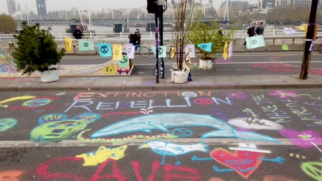 environmental street art is seen on the road as environmental campaigners continue to block waterloo bridge during the second day of a coordinated... - ランベス点の映像素材/bロール