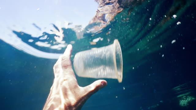 vídeos de stock e filmes b-roll de environmentalist volunteer on plastic in the ocean clean up - copo descartável