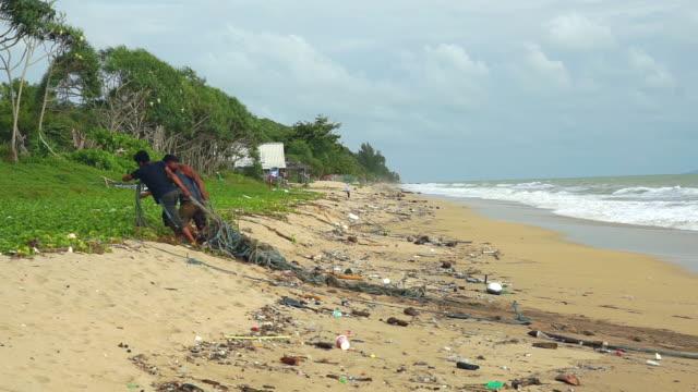 vídeos y material grabado en eventos de stock de environmentalists removing fishing net pollution on beach clean up - red sea
