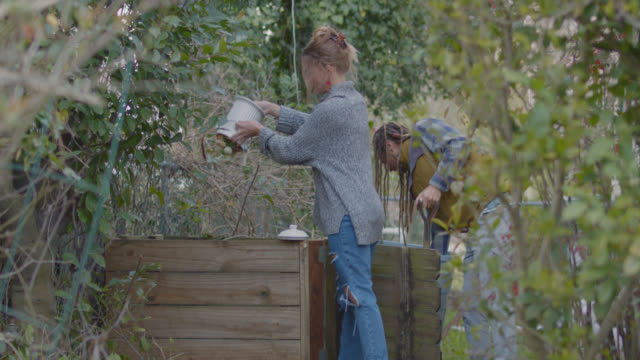 vidéos et rushes de environmentally conscious couple with dog deposits organic material into compost bin outdoors - développement durable