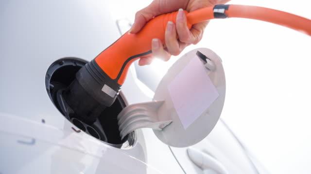 vídeos y material grabado en eventos de stock de mujer consciente del medio ambiente que conecta el coche eléctrico a la estación de carga del vehículo eléctrico - brightly lit
