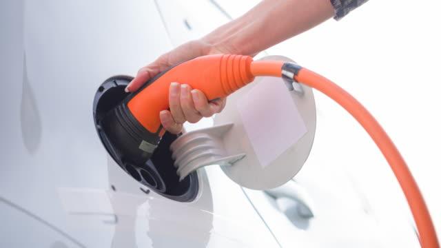 vídeos de stock, filmes e b-roll de mulher ambiental consciente que conecta o carro elétrico à estação de carregamento do veículo elétrico - posto de carregamento de veículos elétricos