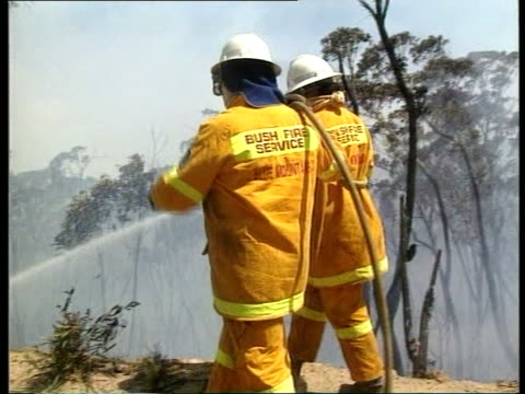 bush fire itn firefighters pushing down unstable walls of burnt out properties firefighters hosing down smoldering undergrowth rod gurney intvwd... - firefighter stock videos & royalty-free footage