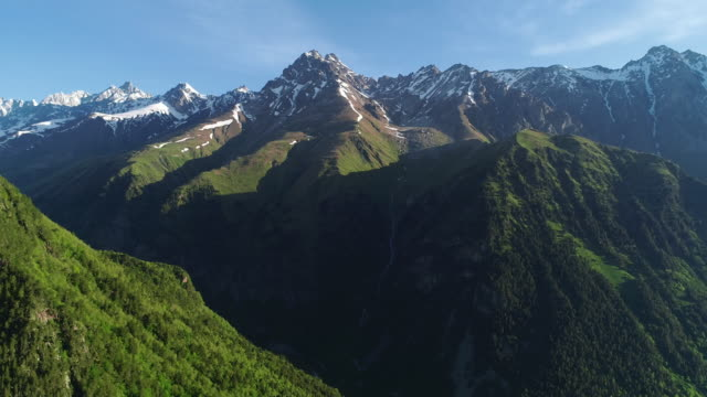 epic aerial close up shot of beautiful mountains with snowy peaks. - mountain stock videos & royalty-free footage