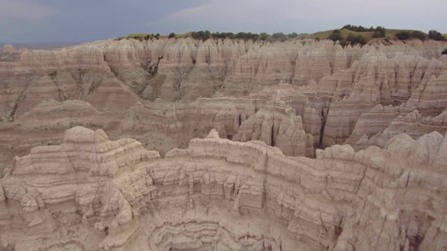DRONE. Epic aerial view of Badlands formations flying back through high rock peaks and steep canyons